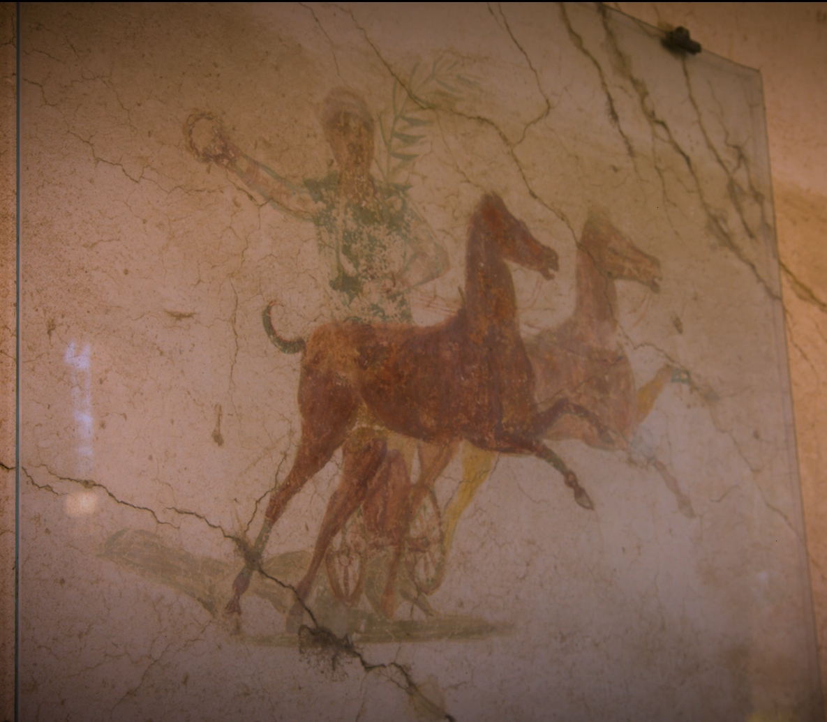 A man on a chariot drawn by two horses going left to right