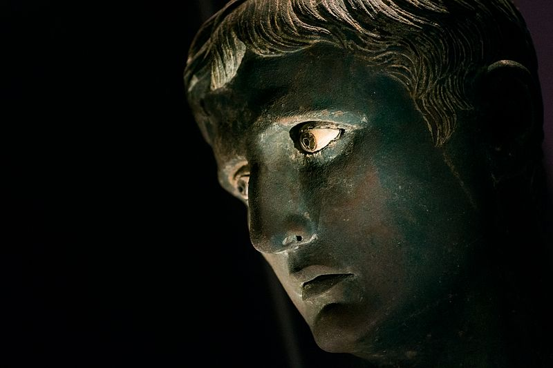 Side view of bronze statue head, against a black background