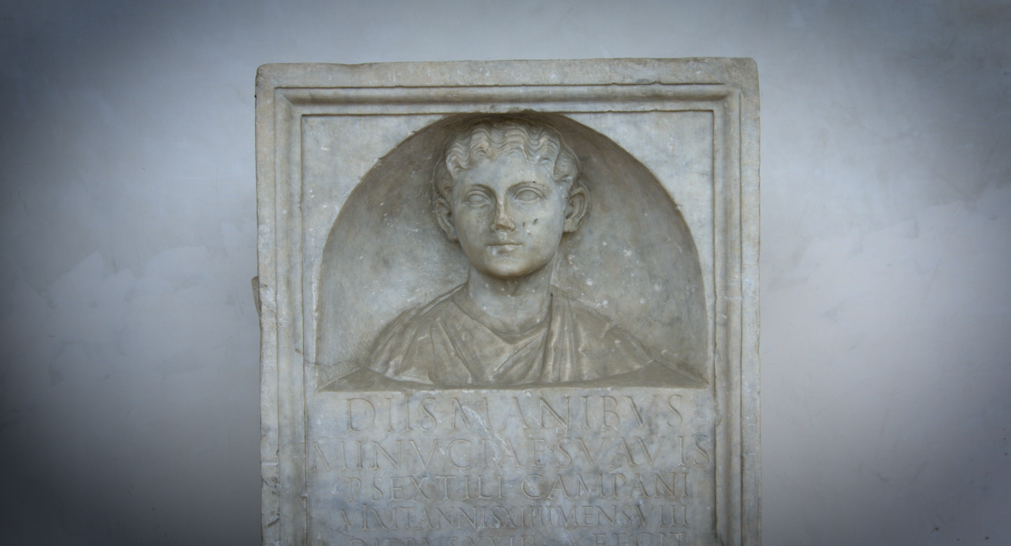 Relief of a woman's head and shoulders above an inscription