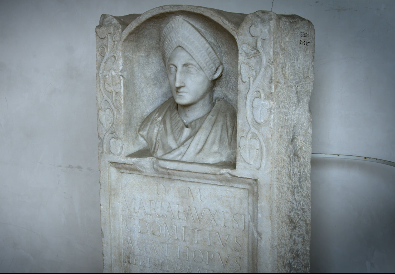 Marble monument with portrait bust of a woman above an inscription
