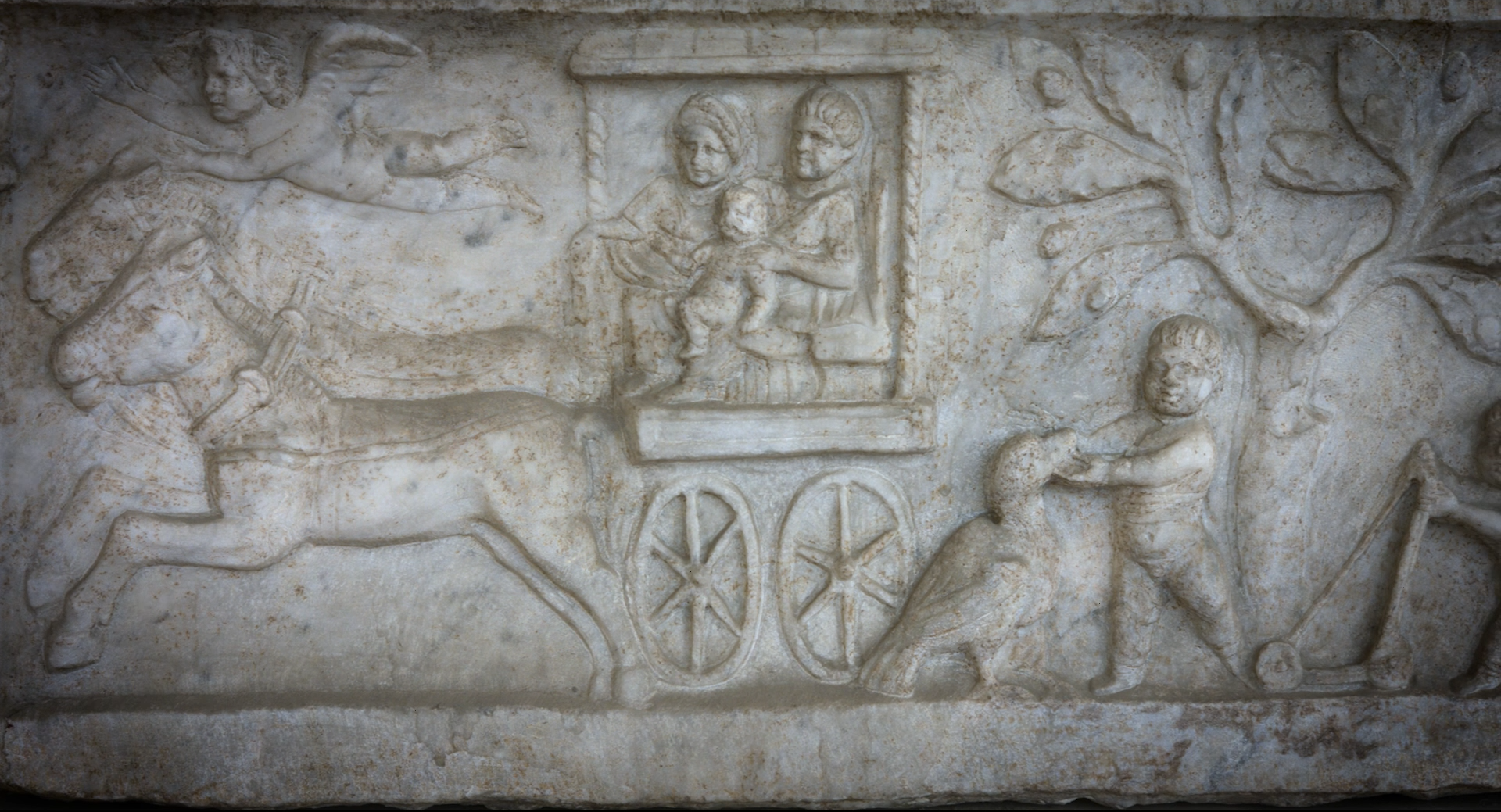 Detail of a marble relief showing figures in a horse drawn cart, and a boy playing with a goose.