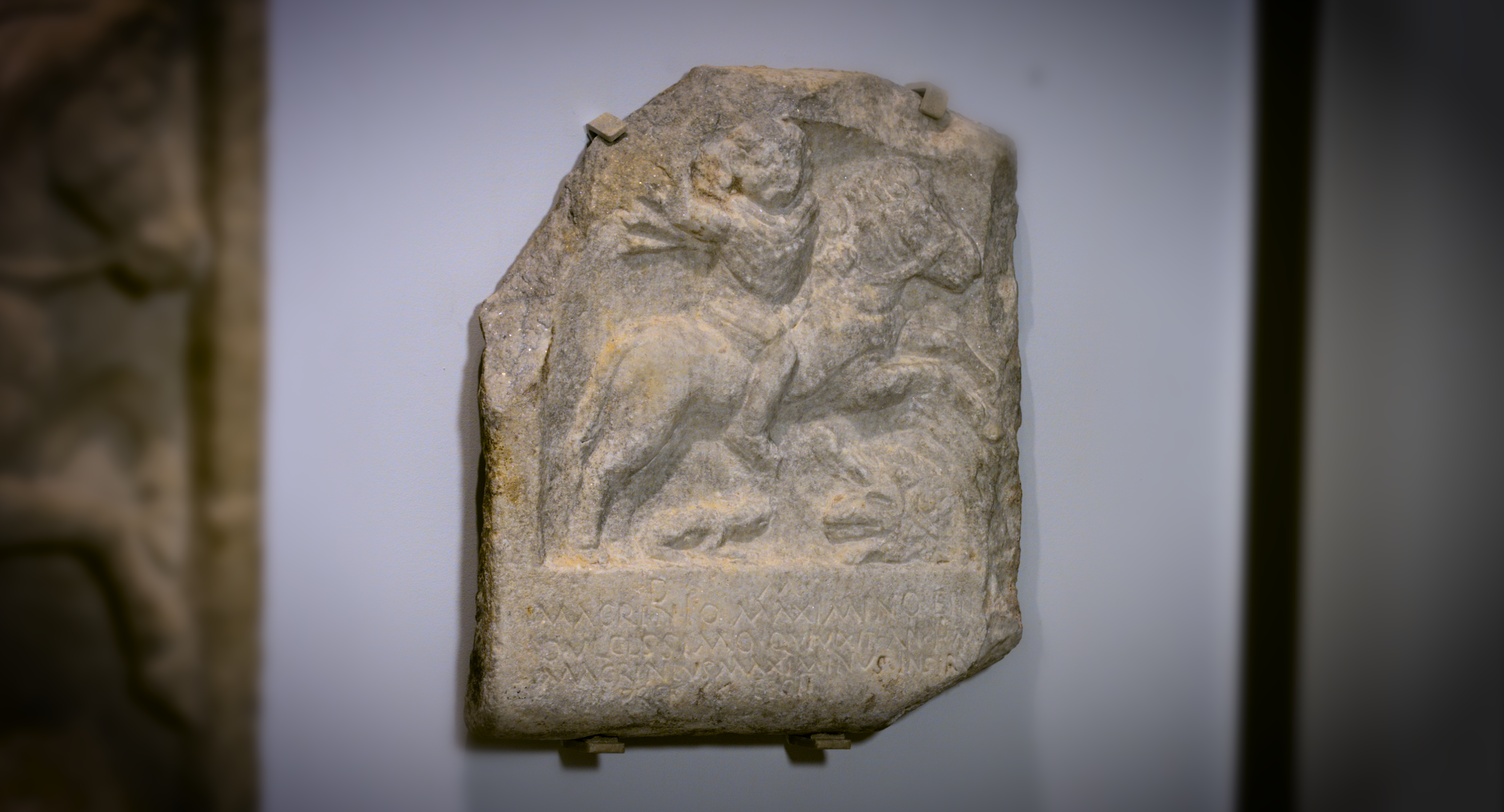 Marble slab with a carving of a figure on horseback and a Latin inscription